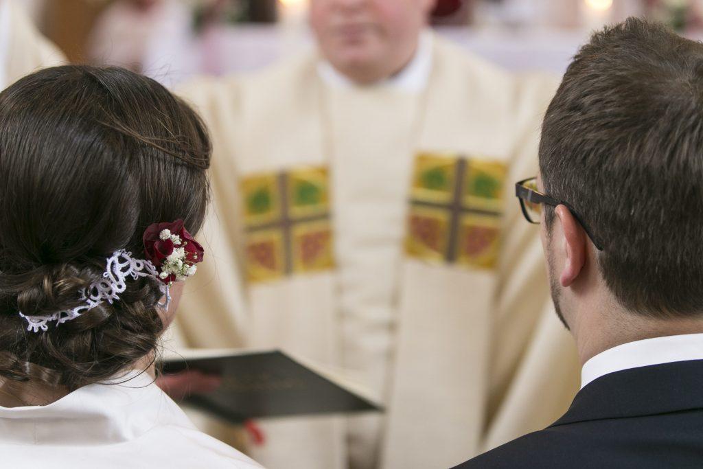 Ein Brautpaar kniet beim Trausegen