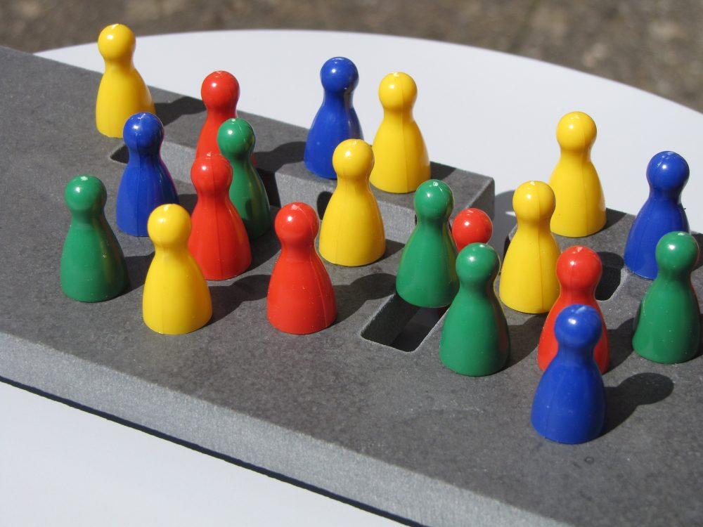 Bunte Spielfiguren auf einem Kreuz