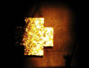 Ein goldenes Kreuz vor einem schwarzen Hintergrund, das von der Sonne beschienen wird.