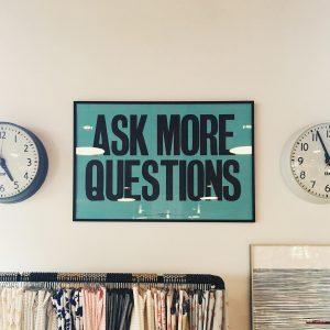 """Zwei Uhren zwischen denen auf Englisch steht """"Stellen Sie mehr Fragen"""""""